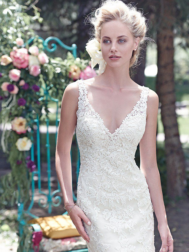 Ten Unique Boho Wedding Dresses - Geddes by Maggie Sottero. Floral lace appliqués, dotted with shimmering sequins, adorn the bodice of this tulle sheath wedding dress, with deep V-neckline and stunning, deep V-back. Finished with covered buttons over zipper closure.
