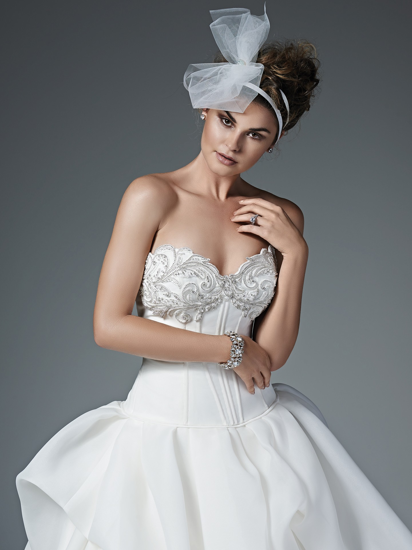 Modern and refined, this Shavon organza ball gown features a stunning pearl and Swarovski crystal encrusted sweetheart neckline and a billowing skirt with delicate pick-ups. Sophisticated exterior boning accents a drop waist. Finished with crystal buttons over zipper and inner corset closure.