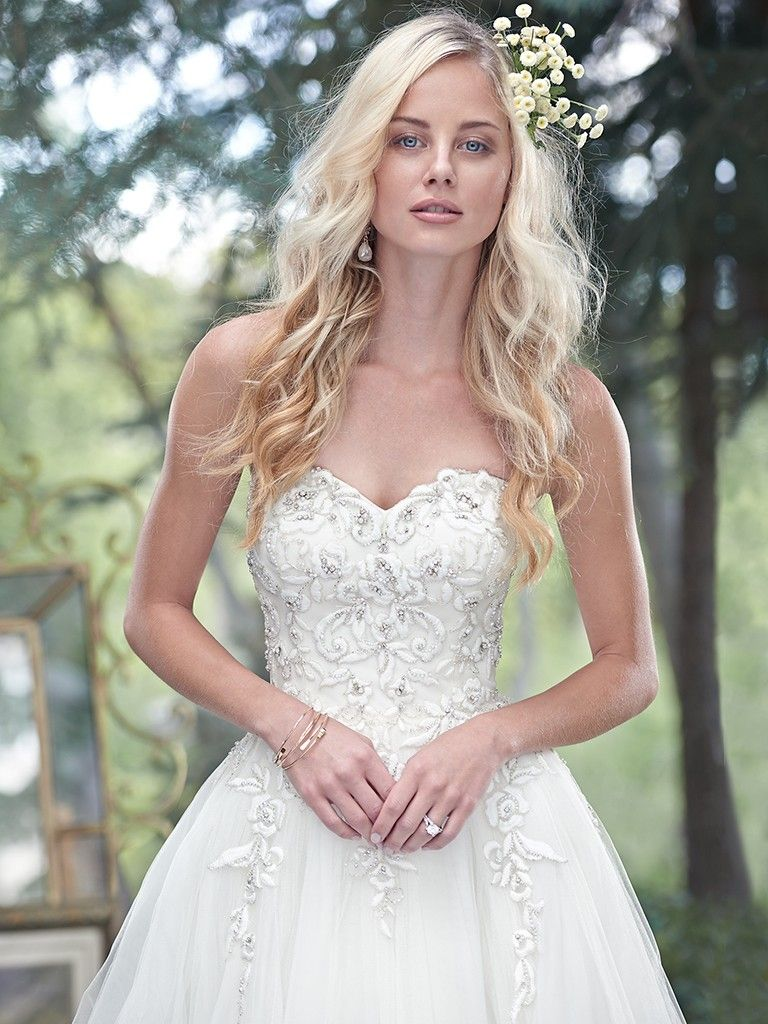 Beautiful ballgowns: Cameron by Maggie Sottero. A fitted bodice, glimmering with lace appliqués dotted with Swarovski crystals, cascades into a full tulle skirt in this whimsical ball gown. A romantic sweetheart neckline completes the look. Finished with zipper over inner corset and crystal button closure.