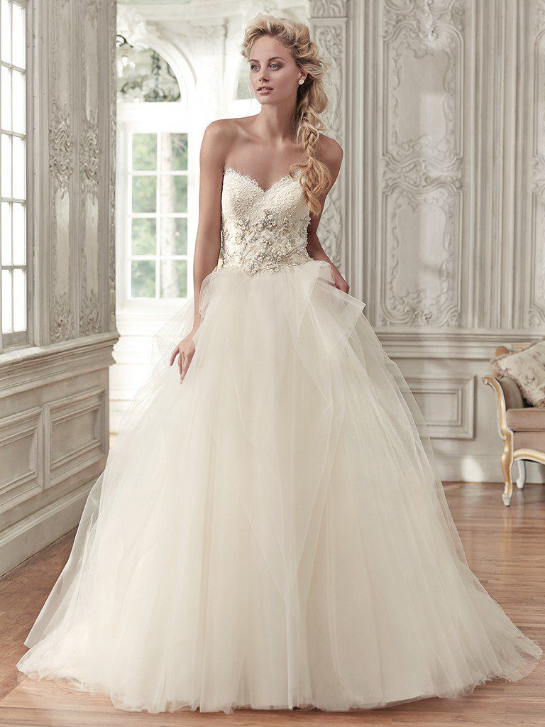 Beautiful ballgowns: Aracella by Maggie Sottero. Elegant glamour is found in this stunning ball gown, featuring a voluminous tulle skirt, romantic sweetheart neckline, and lace bodice, accented with metallic embroidery and glittering Swarovski crystals. Finished with pearl buttons over zipper and inner corset closure.
