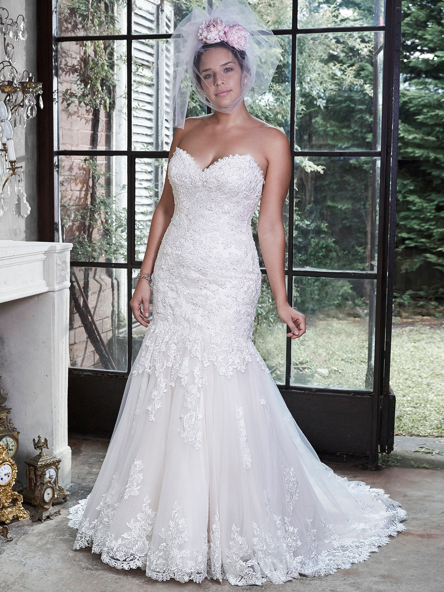 Marianne blush wedding dress. Beautifully embellished lace adorns this dramatic fit and flare wedding gown, with a sweetheart neckline and subtle sparkle. Blush wedding dresses by Maggie Sottero.