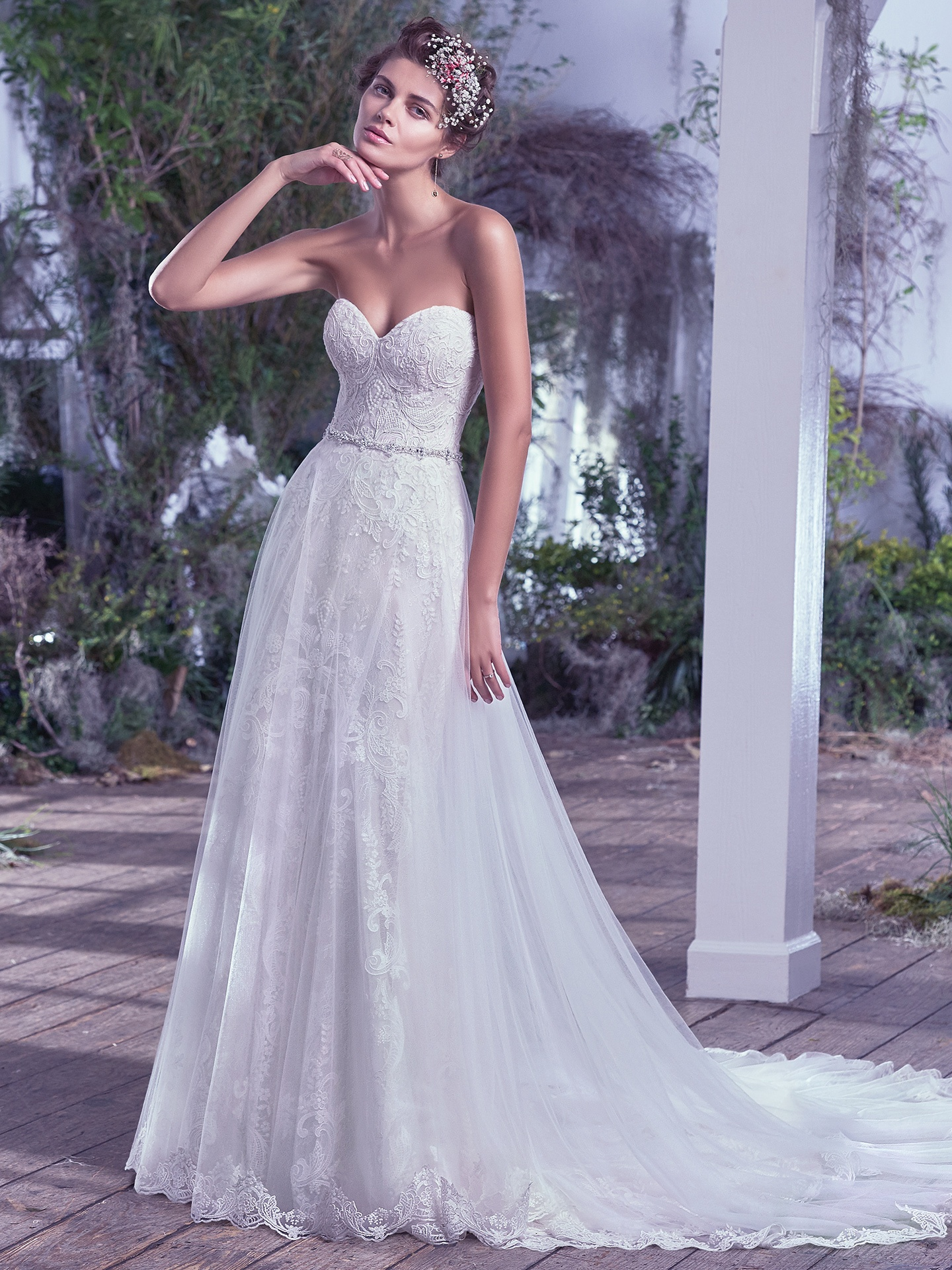 Mirelle by Maggie Sottero. Soft and romantic, this tulle and lace sheath wedding dress, with hand-placed lace appliqués is effortlessly elegant. The sweetheart neckline, natural waist, and scalloped hemline emphasize the ultra-feminine shape.