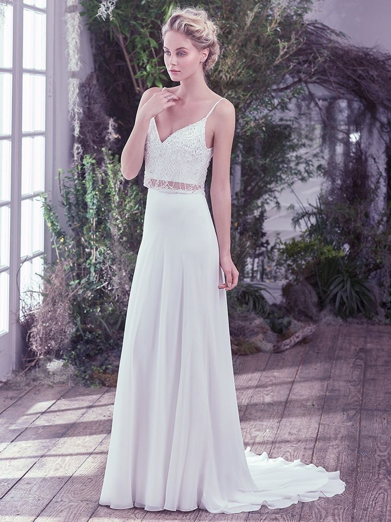 Boudoir Photoshoot Inspiration and Boudoir Inspired Wedding Dresses - Griffyn by Maggie Sottero. Effortlessly chic, this Arlo chiffon and tulle two-piece wedding dress, with a Swarovski crystal and tonal bead embellished bodice overlay and sheer midriff, adds an ethereal twist to this classic sheath silhouette. Complete with a soft V-neckline and scoop back. Finished with zipper closure.
