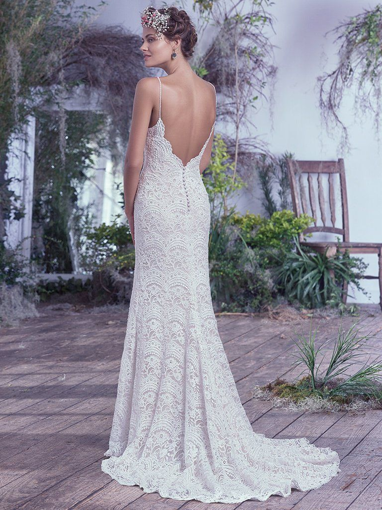 Boudoir Photoshoot Inspiration and Boudoir Inspired Wedding Dresses - Mietra by Maggie Sottero. This intricately woven allover embellished lace wedding dress is highlighted with delicate beaded spaghetti straps, a plunging illusion lace neckline, and a stunning open back. These features add subtle sexy touches to this ethereal sheath wedding gown. Finished with covered buttons over zipper closure.