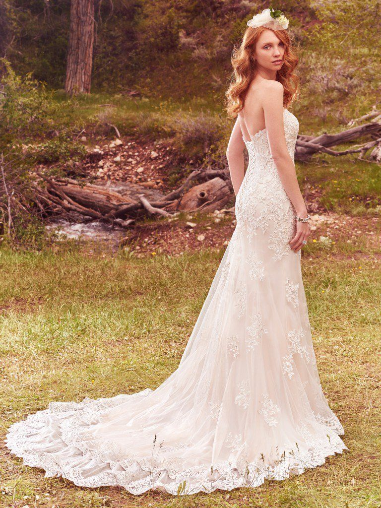 Lace appliqués cascade down this lightweight fit-and-flare, featuring an alluring sweetheart neckline and striking lace hem. - Reynold wedding dress by Rebecca Ingram