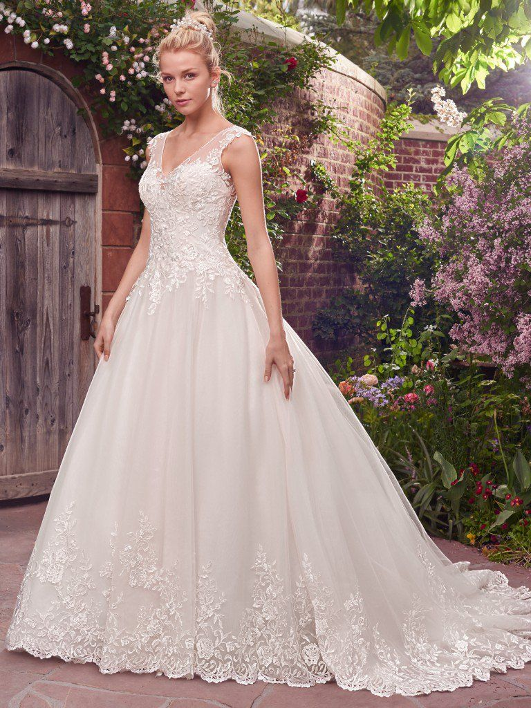 Beautiful ballgowns: Jamie by Rebecca Ingram. Beaded lace appliqués cascade across the gorgeous hemline and bodice in this enchanting ballgown, featuring an illusion V-neckline and illusion back accented with lace. Finished with covered buttons over zipper closure.
