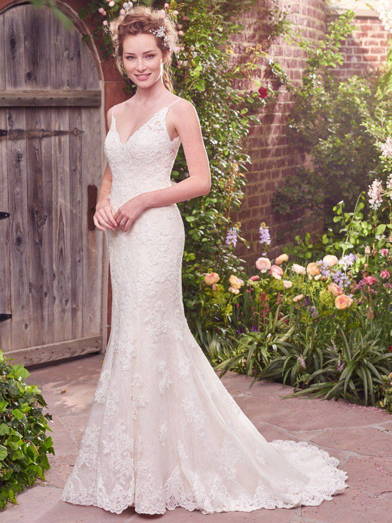 Slip Style Wedding Dresses For Chic and Relaxed Brides. Beaded lace motifs cascade over a layer of Chantilly lace in this fit-and-flare wedding dress, featuring a V-neckline and V-back with illusion lace trim. Delicate scalloping along the neck and hem evokes elegant charm. Finished with crystal buttons over zipper closure. Drew by Rebecca Ingram