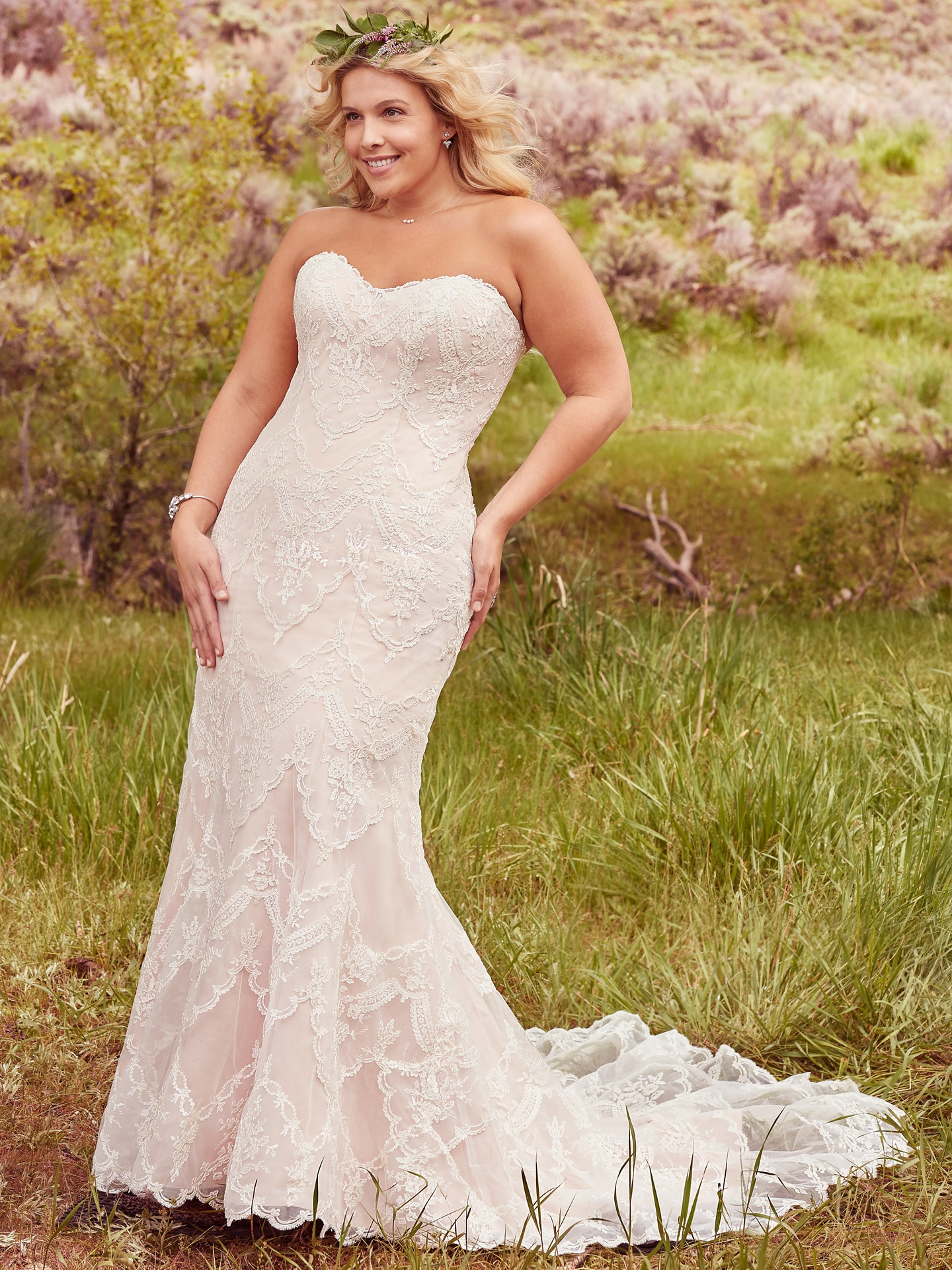 Kirstie by Maggie Sottero. Elegant lace appliqués drift atop tulle to create this breathtaking boho wedding dress with sheath silhouette, with a timeless, romantic sweetheart neckline.