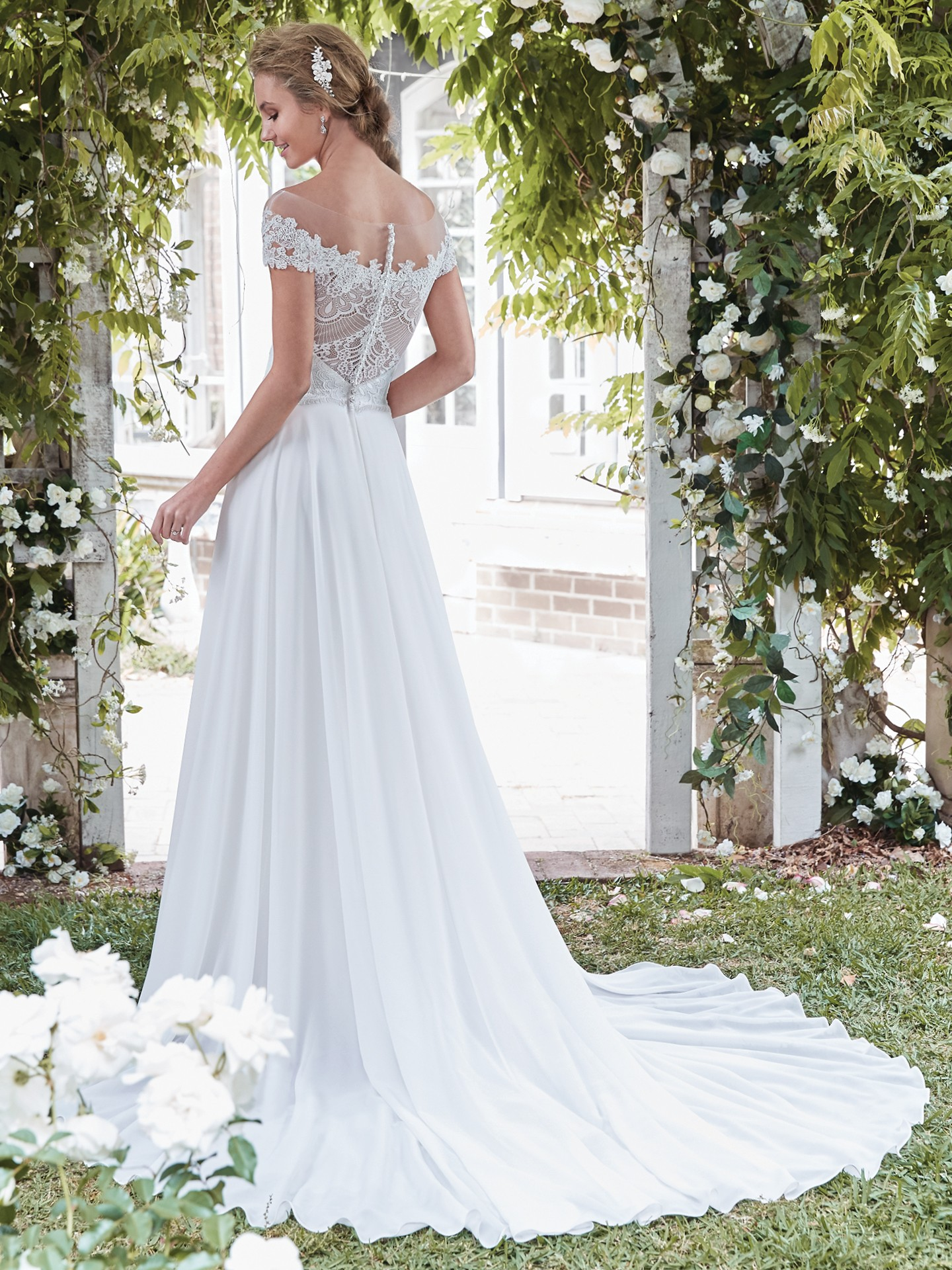 Beatrice by Rebecca Ingram. This vintage-inspired wedding dress features a Verona Chiffon sheath skirt, an elegant lace bodice, and sheer lace comprising the illusion off-the-shoulder over sweetheart neckline and illusion open back. Finished with pearl buttons over zipper closure.