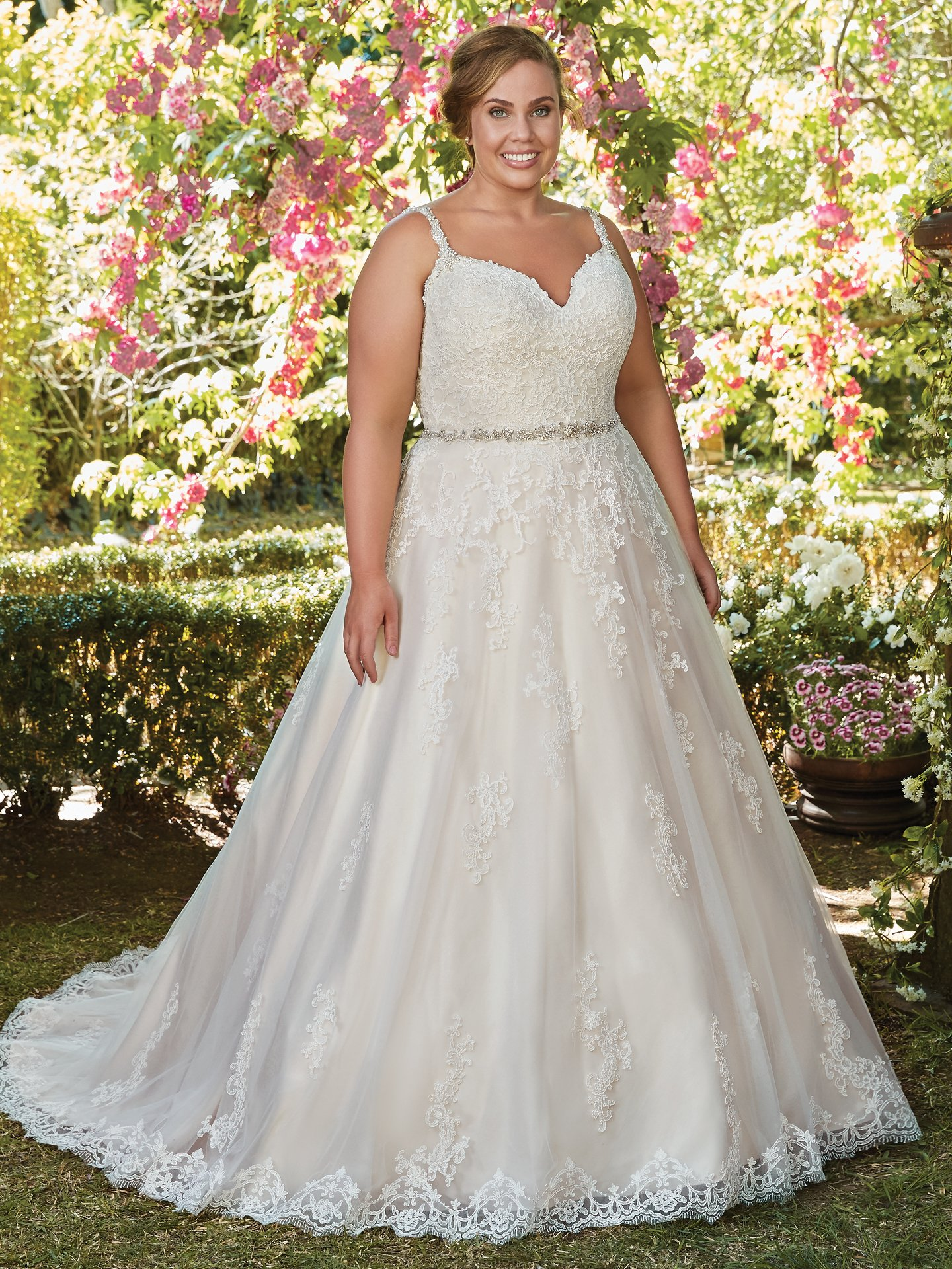 Allison by Rebecca Ingram. This gorgeous ballgown features a layer of lace appliqués over tulle. A V-neckline and open back with lace illusion trim add hints of alluring romance to this princess wedding dress. Accented with Swarovski crystal belt and embellished straps. Finished with covered buttons and zipper closure.