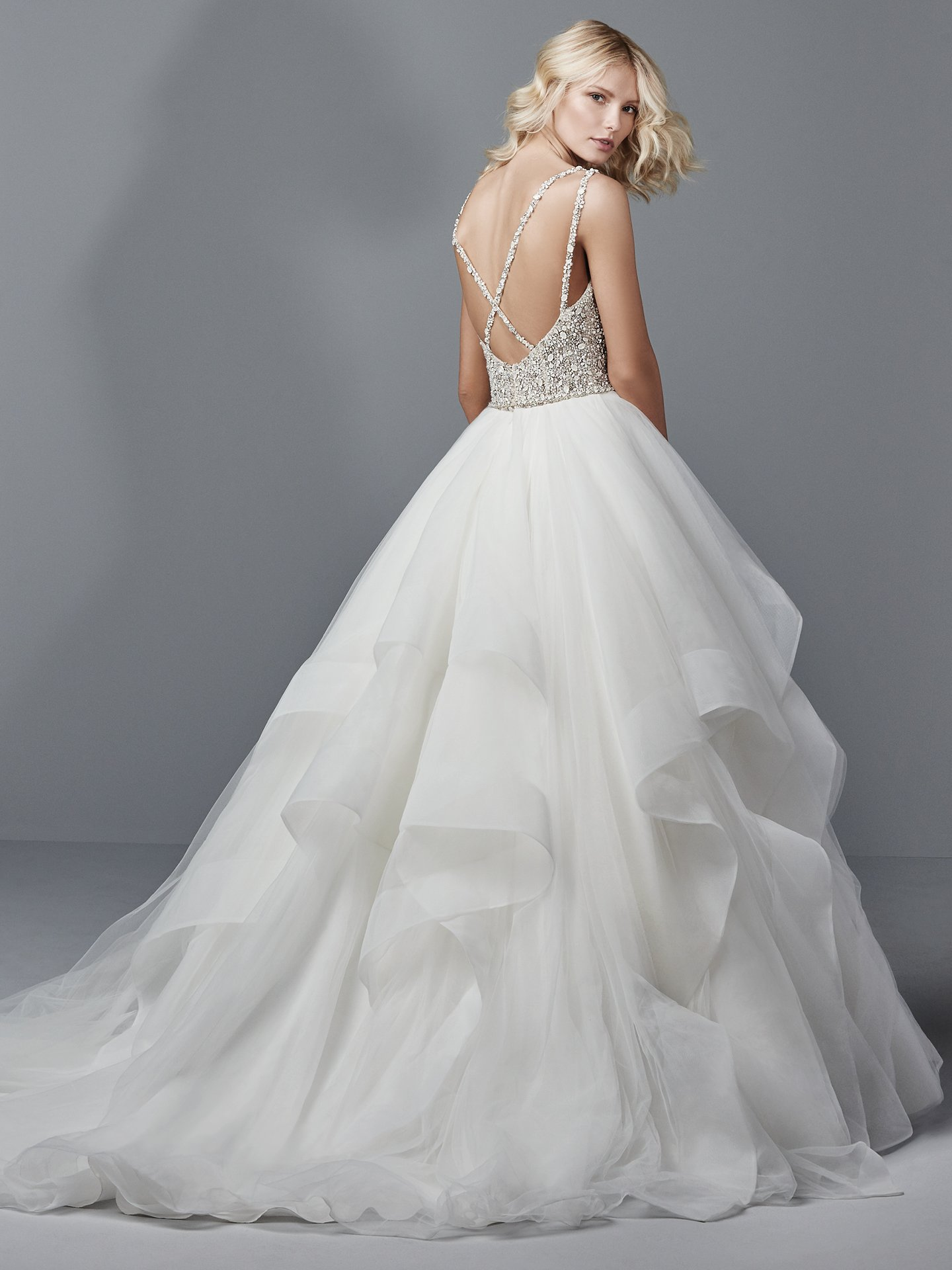 Micah by Sottero and Midgley. This princess wedding dress features a bead and Swarovski crystal-encrusted bodice atop a tiered ballgown skirt of tulle and horsehair. Double spaghetti straps glide from the V-neck into a crisscross pattern over the scoop back. Finished with crystal buttons over zipper closure. Detachable beaded belt sold separately. Princess Ballgowns For Royal Weddings