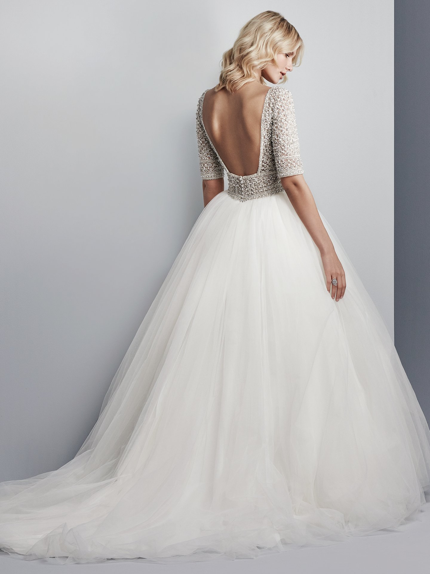 Allen by Sottero and Midgley. This show-stopping ballgown features a sheer bodice of Swarovski crystals and beading atop a voluminous tulle skirt. Complete with half-sleeves, an elegant illusion bateau over sweetheart neckline, and sexy open back. Finished with crystal buttons over zipper closure. Princess Ballgowns For Royal Weddings