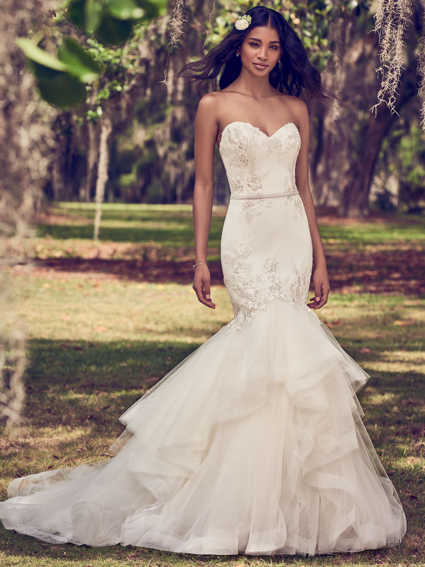 This mermaid wedding dress features a tulle bodice accented in embroidered lace motifs atop a tiered tulle fit-and-flare skirt edged in horsehair. Complete with strapless sweetheart neckline and bead and pearl embellished belt. Lined with shapewear for a figure-flattering fit. Available in Ivory with Pewter Accent. Dalinda by Maggie Sottero. Colorful Wedding Dresses For The Bold Bride