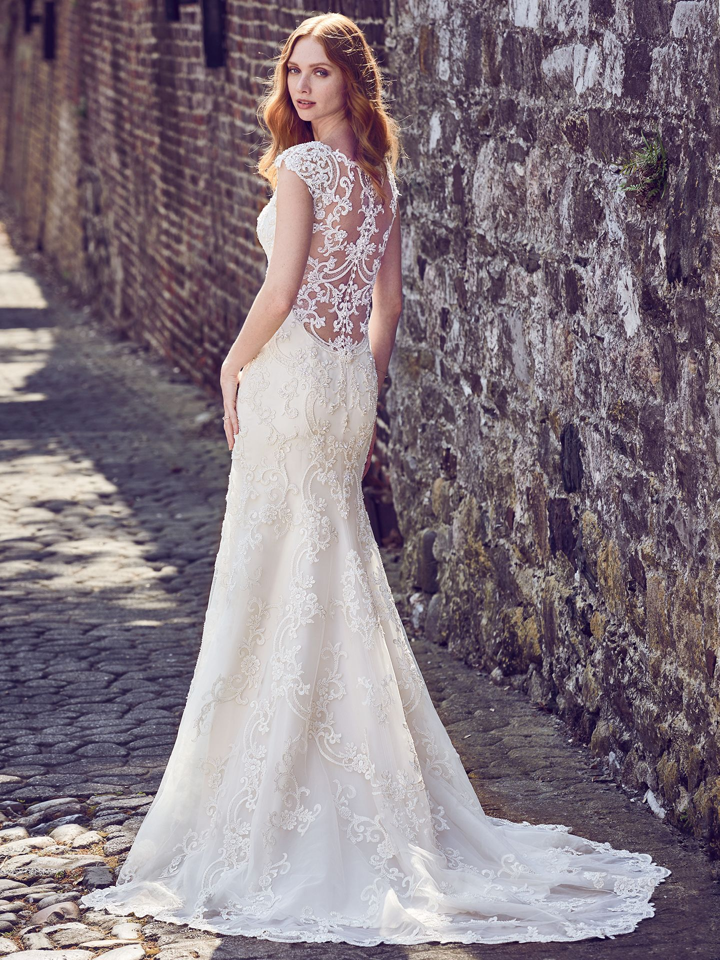Everly by Maggie Sottero. This elegant fit-and-flare wedding dress features a tulle overlay of beaded lace motifs, creating an illusion bateau over sweetheart neckline, illusion cap-sleeves, illusion scoop back, and beautiful scallop hemline. Finished with pearl buttons and zipper closure. Upcoming 2018 wedding dress trends from Maggie Sottero!
