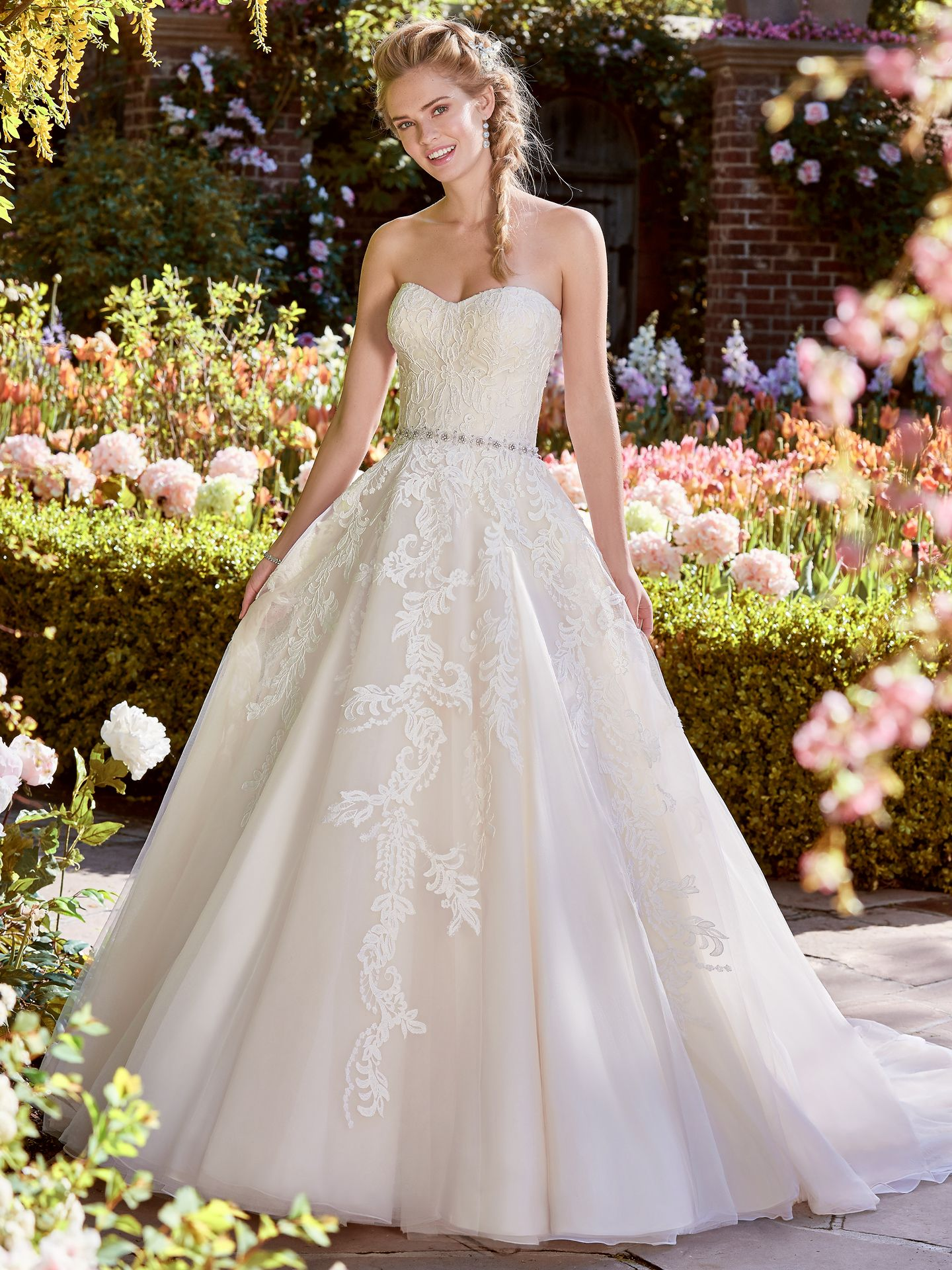 Bernice by Rebecca Ingram. This royal wedding dress features a bodice of lace motifs atop a tulle skirt. A strapless scoop neckline and beaded belt accented in Swarovski crystals complete the romance of this Ballgown. Finished with covered buttons and zipper over inner corset closure. Princess Ballgowns For Royal Weddings