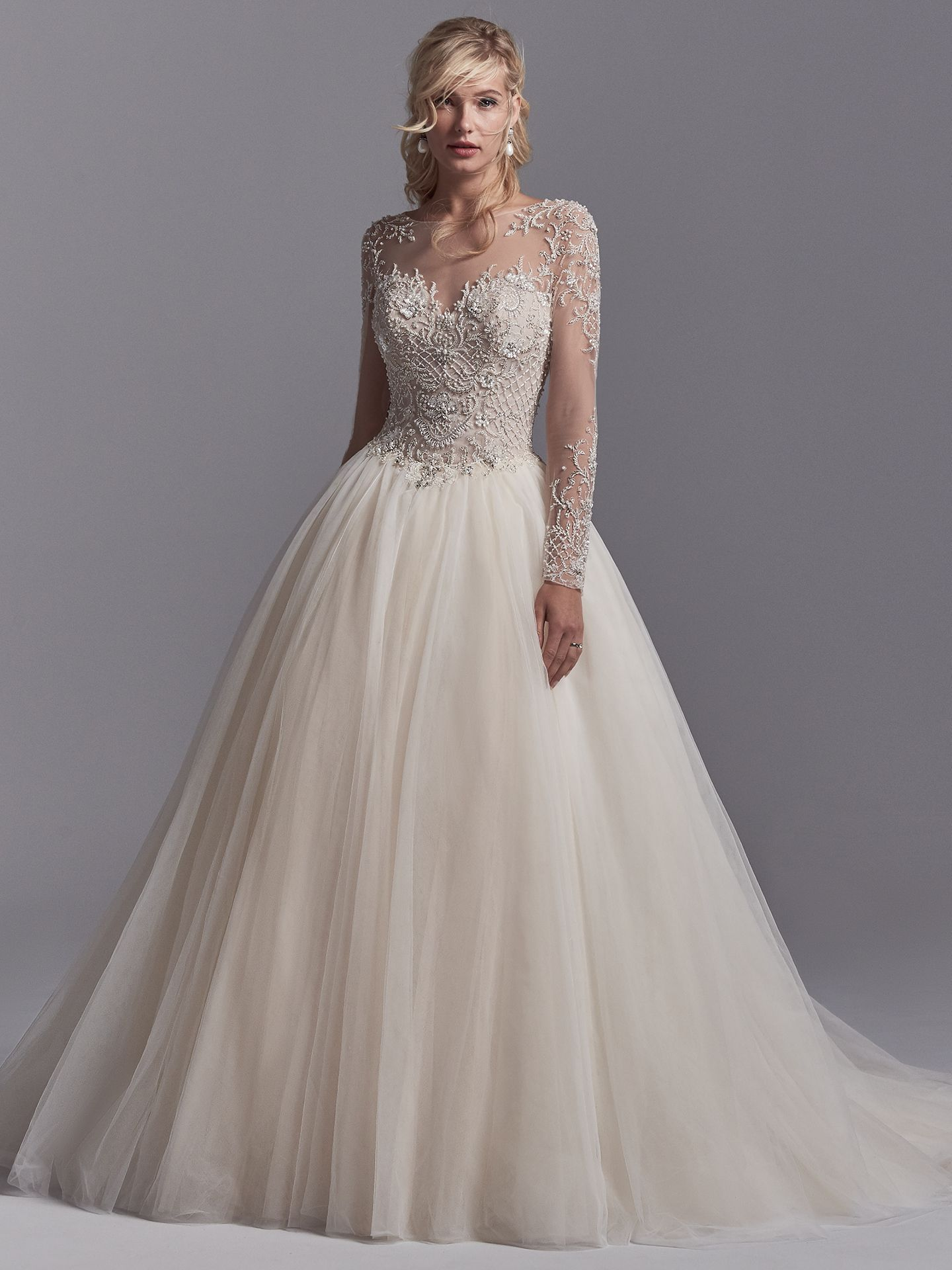 Calvin by Sottero and Midgley. This sleeved wedding gown features a bodice of beaded lace motifs accented in Swarovski crystals, accenting the illusion long-sleeves, illusion sweetheart neckline, and illusion V-back. Layers of tulle create the ballgown skirt. Finished with covered buttons over zipper closure. Princess Ballgowns For Royal Weddings