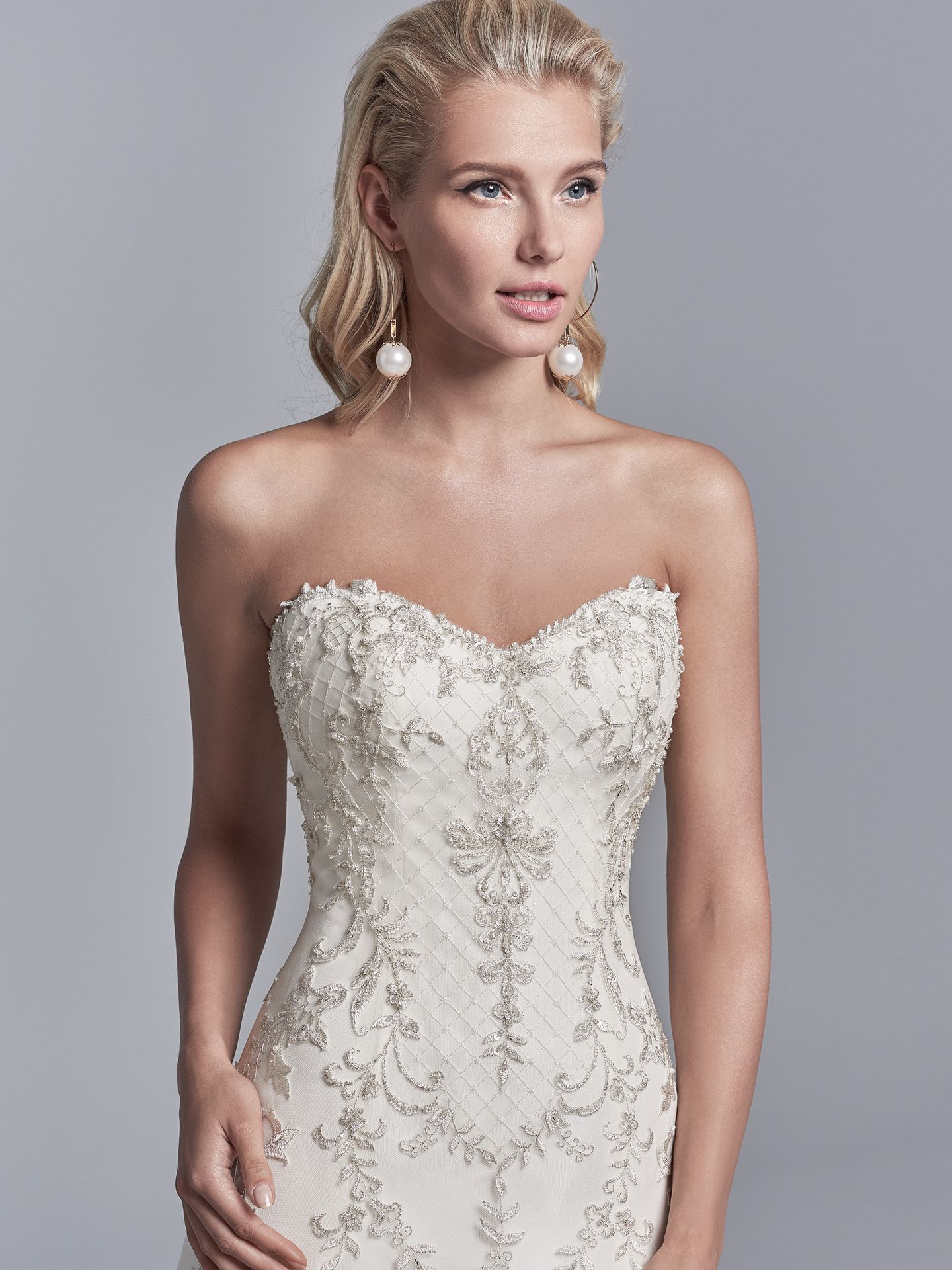 Granger by Sottero and Midgley. Embroidered lace motifs and Swarovski crystals dance over this tulle and Soft Shimmer Satin A-line wedding gown, featuring a strapless sweetheart neckline, illusion scoop back accented in beaded lace motifs, and crosshatch detail through the hemline. 10 Top-Pinned Sottero and Midgley Gowns of 2017.