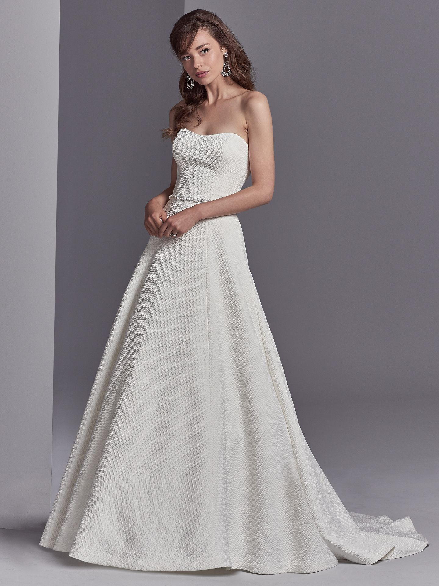 Comprised of Alodia specialty textured fabric, this unique A-line wedding dress features a beaded belt accented in Swarovski crystals and a strapless scoop neckline. Lined with shapewear for a figure-flattering fit. - The Latest Wedding Dress Trends for Engagement Season 2018