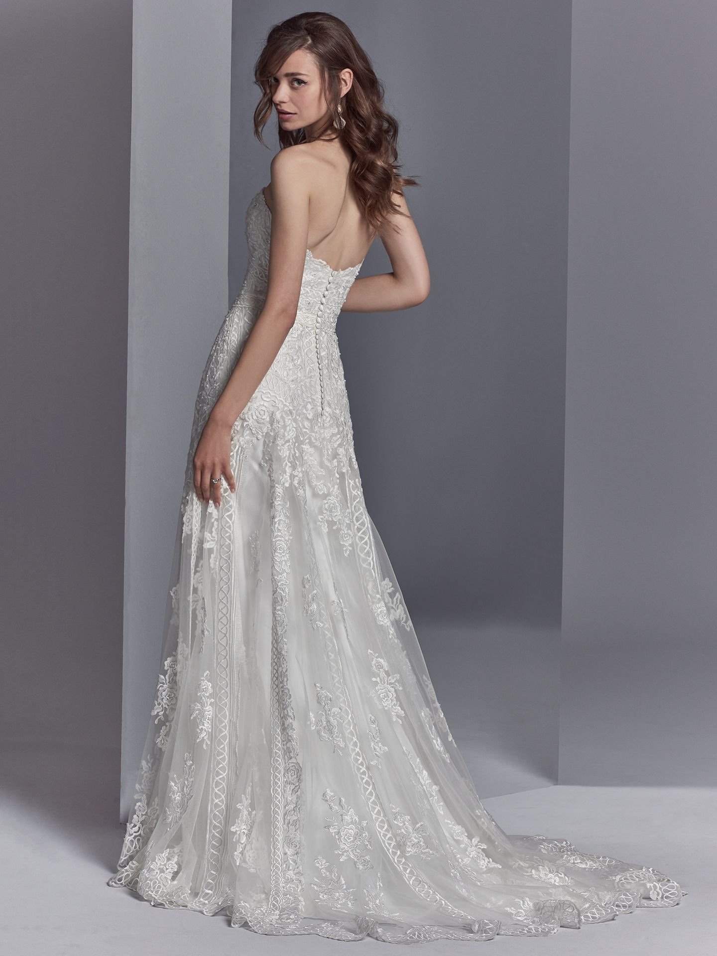 Skylar by Sottero and Midgley. Embroidered lace motifs accented in beading and Swarovski crystals cascade over tulle in this sheath wedding dress, completing the strapless sweetheart neckline and scallop lace hemline. 10 Top-Pinned Sottero and Midgley Gowns of 2017.