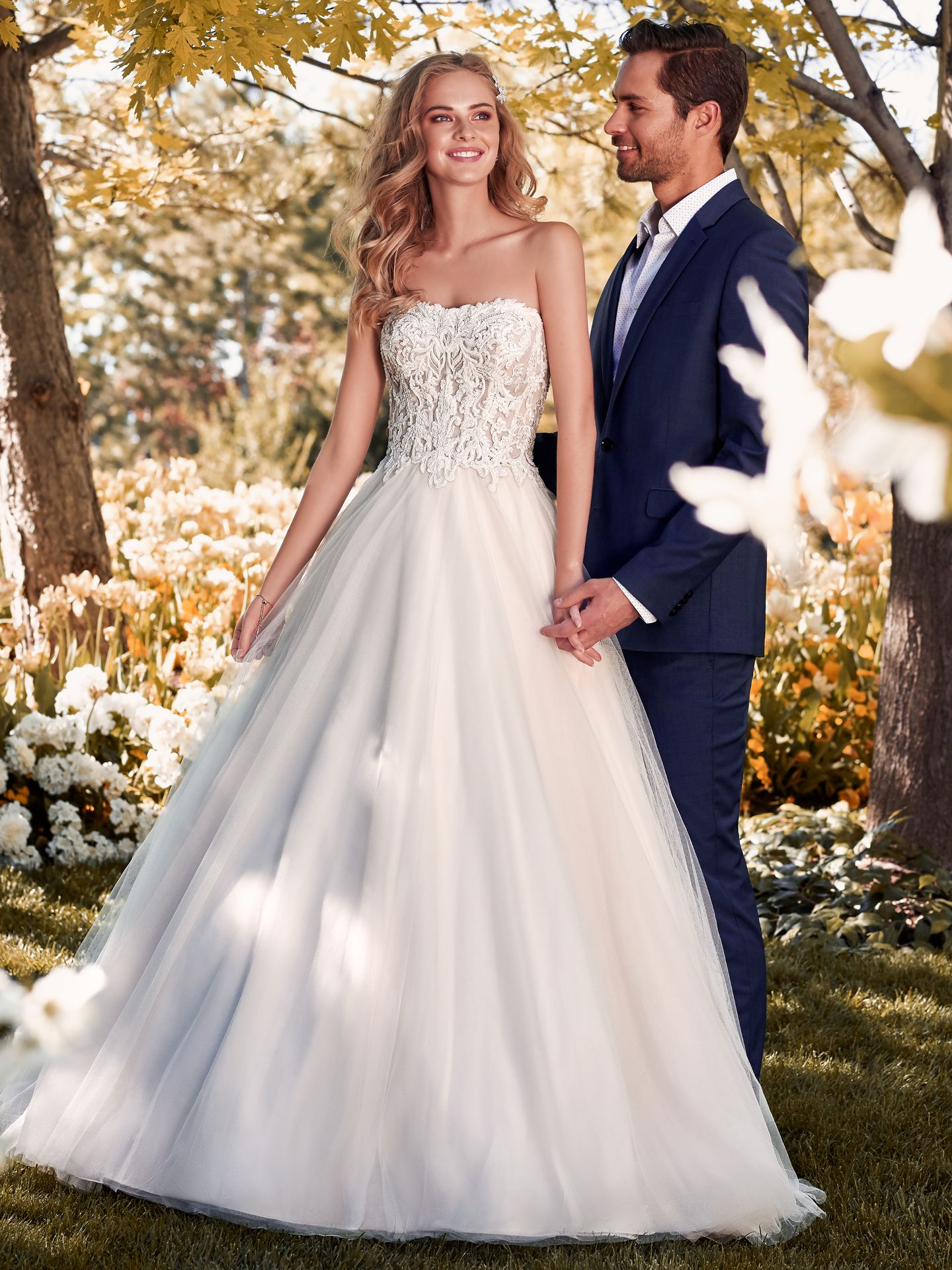 Lavonne by Rebecca Ingram. This princess wedding dress features a sheer bodice accented in exposed boning and beaded lace motifs. Ballgown skirt comprised of tulle. Complete with strapless scoop neckline. Finished with pearl buttons over zipper closure.