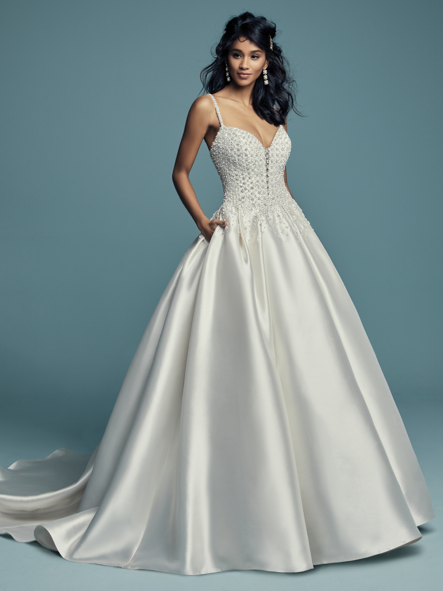 Dana by Maggie Sottero. Delicate beaded motifs adorn the bodice of this Elodie Mikado princess wedding dress, drifting into a billowing ballgown skirt with pockets. Beaded spaghetti straps complete the illusion plunging sweetheart neckline. Finished with crystal buttons over zipper closure.