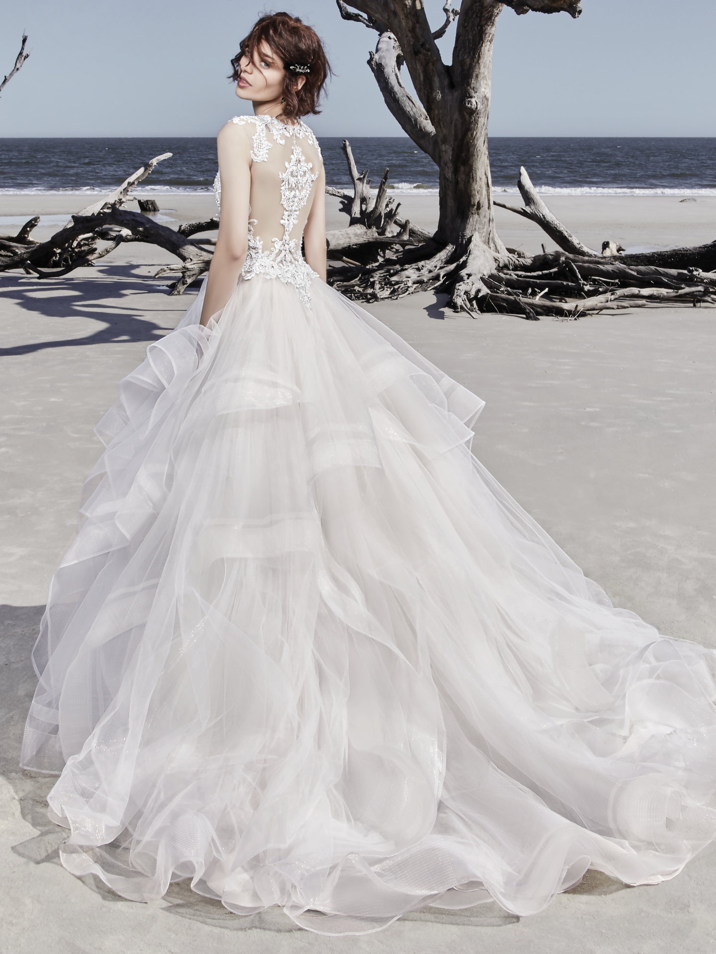 Ariya by Sottero and Midgley. This modern princess ballgown features a beaded lace bodice, accented in Swarovski crystals, atop a tiered tulle skirt trimmed in horsehair. Beaded lace motifs complete the unique illusion jewel neckline and statement illusion back. Finished with crystal buttons and zipper closure. Princess Ballgowns For Royal Weddings