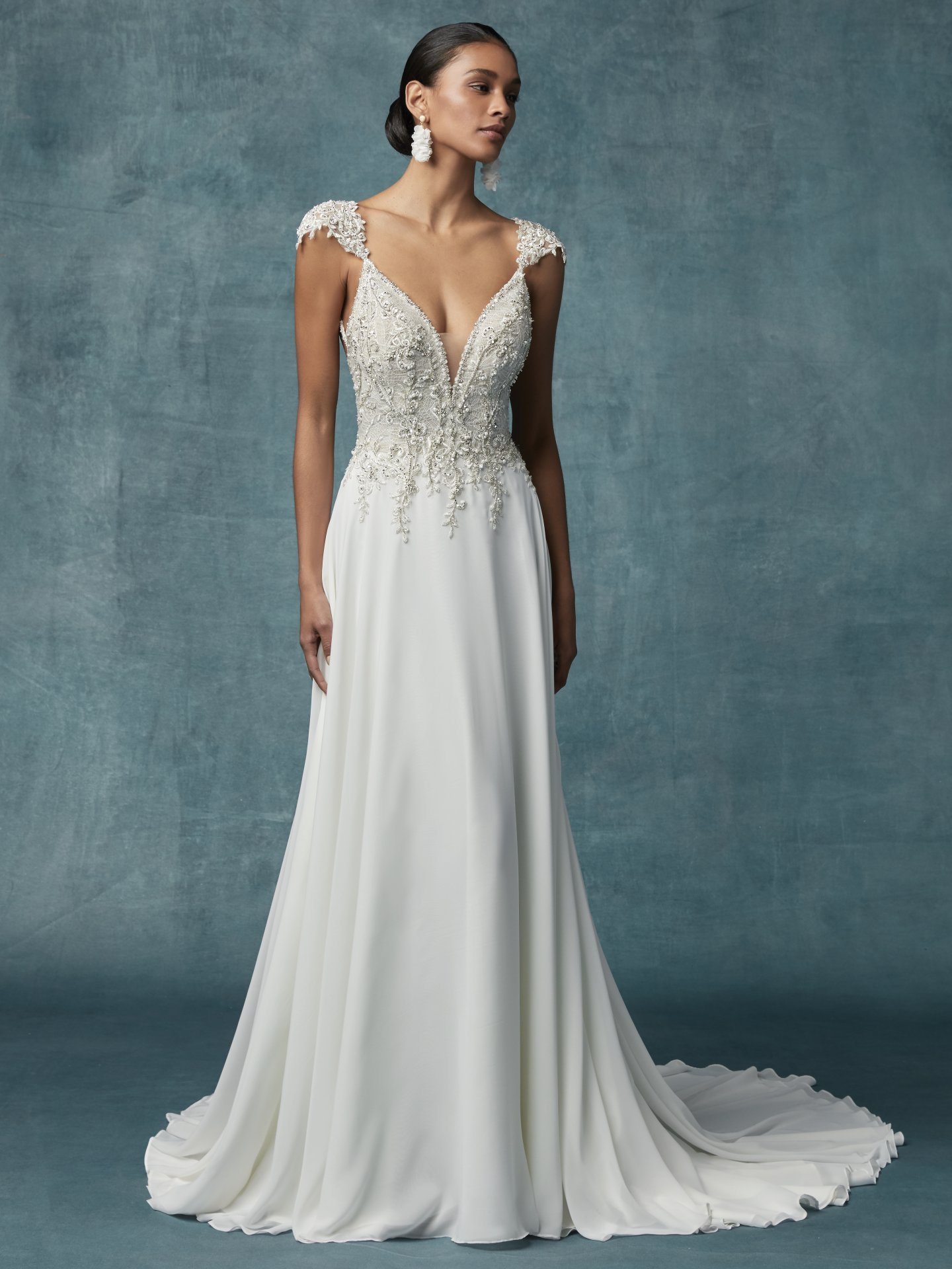 Beaded cap-sleeves and Grecian-inspired wedding dress features a bodice accented in beaded lace motifs and Swarovski crystals atop a Georgette chiffon A-line skirt. Fabulous Wedding Dresses With a Variety of Beaded Sleeves