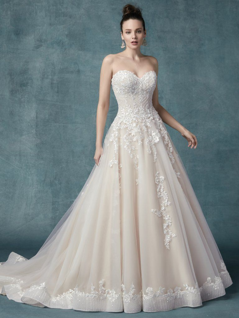 Ivory over blush wedding dress. Zinaida by Maggie Sottero. Floral lace motifs dance over tulle in this unique princess ballgown, accenting the geometric embroidery and beading on the bodice, sweetheart neckline, and hemline. Complete with covered buttons over zipper and inner elastic closure.
