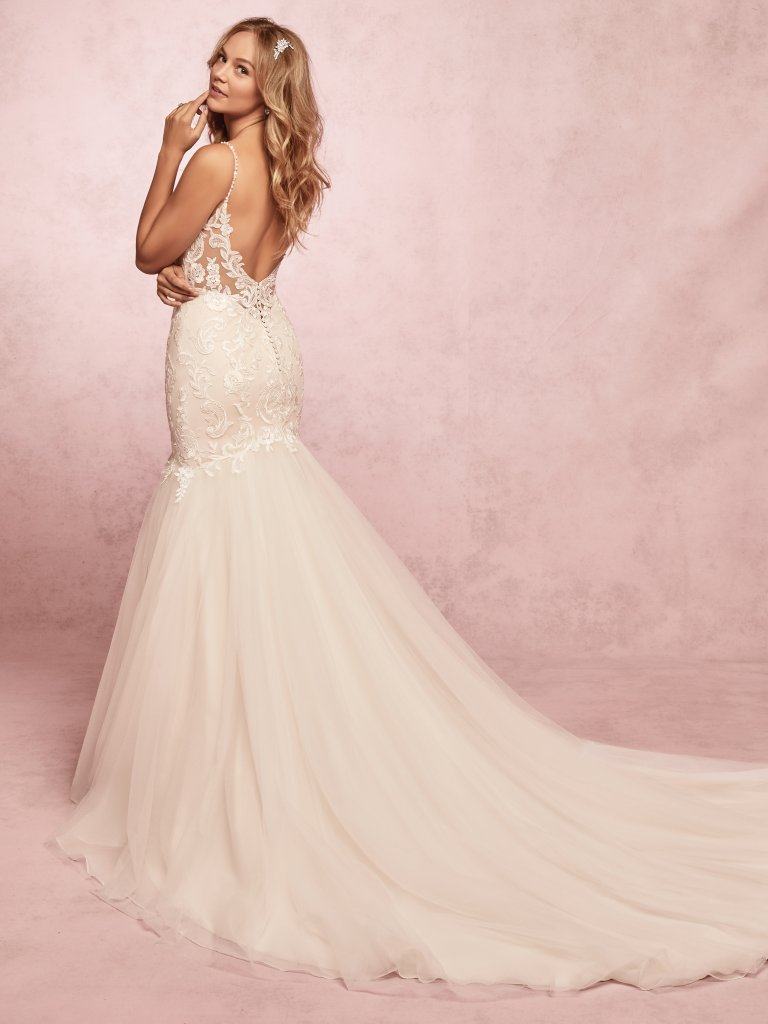 Fawn by Rebekah Ingram. This soft blush fit-and-flare wedding gown features a lace-embellished bodice over a tulle skirt. Lace motifs adorn the sweetheart neckline and illusion scoop back. Complete with beaded spaghetti straps.
